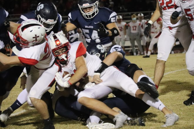 Shawnee defensive lineman Lane Williams (67) wraps up the Tulsa Bishop Kelley ball carrier while teammate Koby Mitchell (54) pursues on the play last Friday night at Jim Thorpe Stadium.