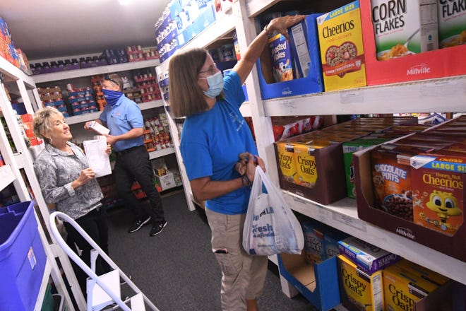 Susan Degnan puts away food at the Christian Community Caring Center in Hampstead. COVID-19 has posed some problems for food pantries in Pender County  and many local businesses have helped collect food donations. [KEN BLEVINS/STARNEWS]