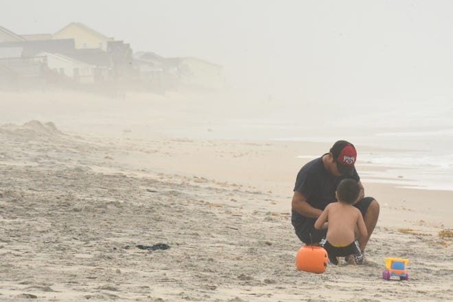 People enjoy the beach in Surf City, N.C. Thursday Nov. 12, 2020, while COVID-19 disrupted some of the summer tourism in beach areas Southeastern N.C. tourism continues this fall. [KEN BLEVINS/STARNEWS]