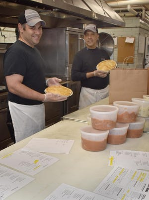 At the Galley Grille Randy Lima and Mike Dabrieo work on packing up takeout orders in this file photo from earlier in the pandemic.