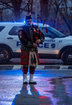 Firefighter Patrick Hayes plays the bagpipe during a memorial service outside the McKeon Road Fire Station in Worcester Friday marking the one year anniversary of the line-of-duty death of Lt. Jason Menard.