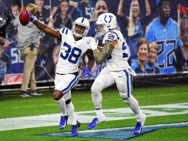 The Colts' T.J. Carrie (38) celebrates with teammate Cassius Marsh after recovering a blocked punt and returning it for a touchdown during the second half against the Titans on Thursday night.