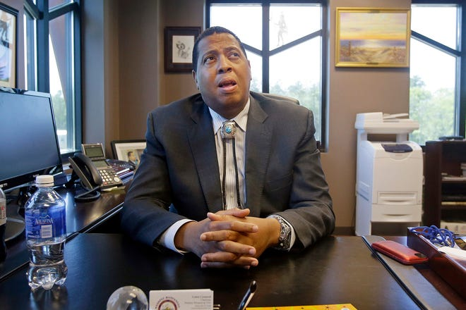 In this May 29, 2014 photo, Mashpee Wampanoag Tribe Chairman Cedric Cromwell sits behind his desk at the government center in Mashpee. Cromwell and the owner of a Rhode Island architecture firm were arrested Friday, and charged in a bribery scheme involving the tribe's plans to build a resort casino in Taunton.