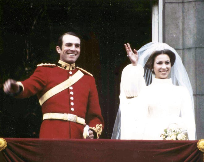 Britain's Princess Anne, daughter of Queen Elizabeth II, with her husband, Captain Mark Phillips of the First Queen's Dragoon Guards, waves from the balcony of Buckingham Palace, London, Nov. 14, 1973, following their wedding in Westminster Abbey.