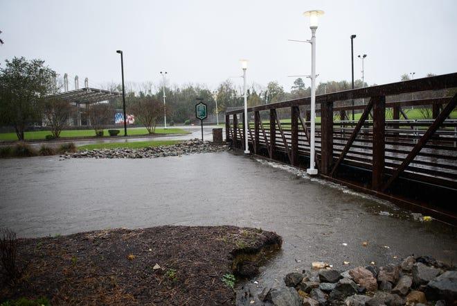 A swollen Cross Creek reaches the underside of the pedestrian bridge to Festival Park on Thursday.