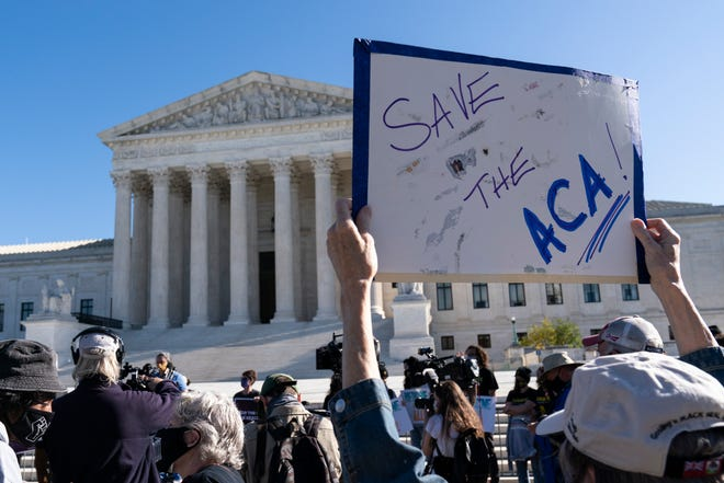 A demonstrator holds a sign in front of the U.S. Supreme Court as arguments are heard about the Affordable Care Act on Nov. 10 in Washington.