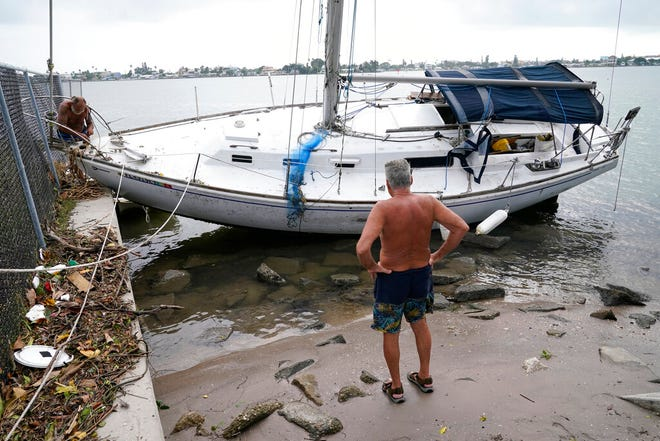 A sailboat is washed ashore in the aftermath of Tropical Storm Eta, Thursday, Nov. 12, 2020, in Madeira Beach, Fla. Eta dumped torrents of blustery rain on Florida's west coast as it slogged over the state before making landfall near Cedar Key, Fla. (AP Photo/Lynne Sladky)