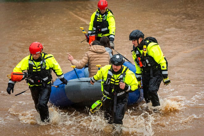 Firefighters with the Winston-Salem Fire Department evacuate residents at Creekwood Apartments as flood waters rise on Thursday, Nov. 12, 2020 in Winston-Salem, N.C. (Andrew Dye/The Winston-Salem Journal via AP)