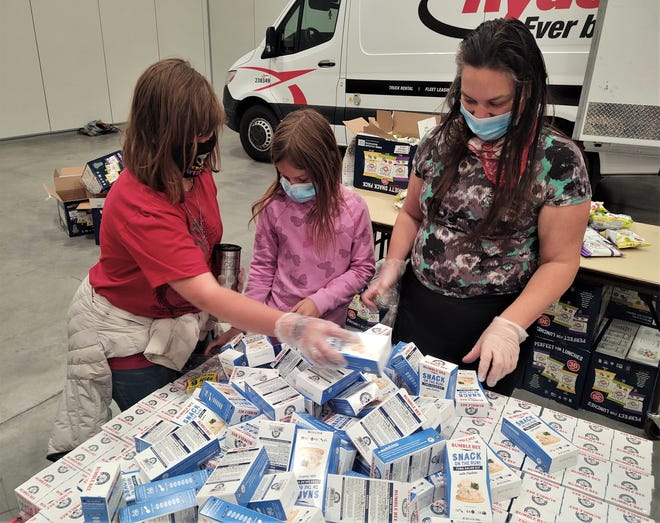 Food kit volunteers, from left, Autumn Naden, Jennavieve Gehlhoff and Kelly Gehlhoff add tuna fish packets to the parcels inside the Pueblo Convention Center Friday.