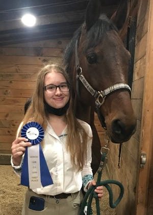 Maddy Penney, of the Maple Grove riding school team, with her horse, Autumn, displays the blue ribbon won by the championship team, in the Interscholastic Equestrian Association competition.  The team, taught by head trainer Brittany Sukis of the Hudson riding school, will compete in the regional IEA competition on Nov. 29 in Oxford.