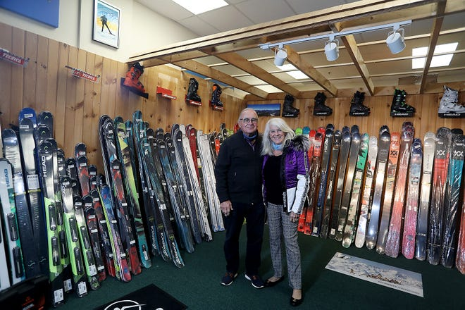 John and Eileen Byrne of Buckles and Boards stand in the loft with the skis and snowboards that they sell at their new store next to the Star Market on Friday, Nov. 13, 2020.