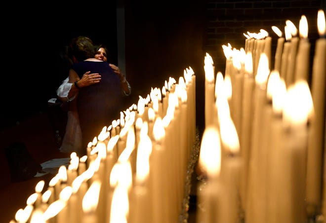 Two people embrace at the end of Thursday's West Texas Rehabilitation Center's Hospice of the Big Country Candlelight Memorial at Hardin-Simmons University's Logsdon Chapel.