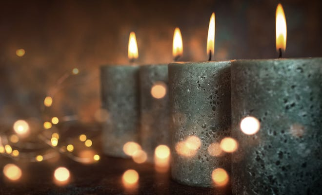 Candles with festive lights in front of dark background