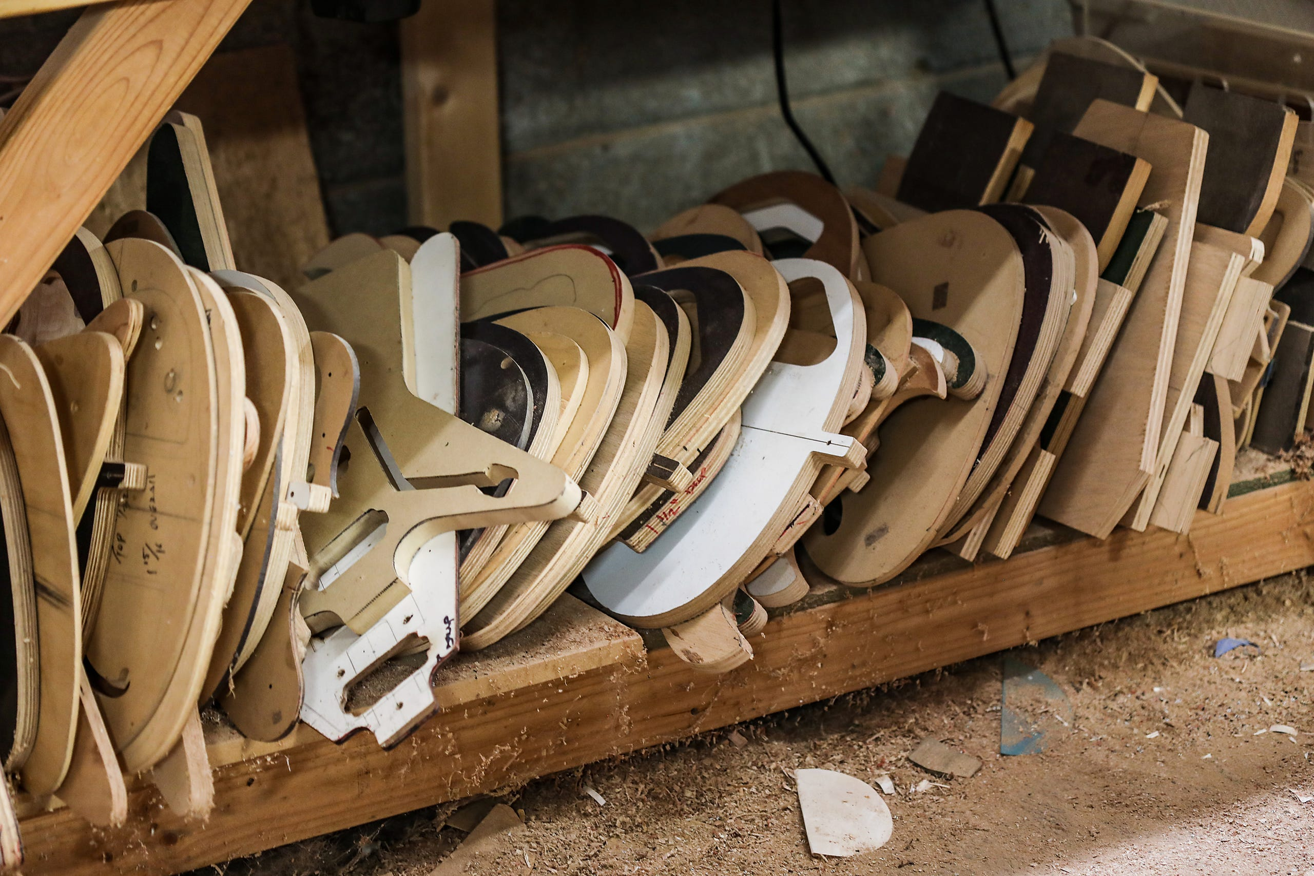 """Guitar bodies line the bottom shelf of Gabriel Currie's woodworking table in his Echopark Guitars' studio in the Old Redford neighborhood of Detroit on Nov. 12, 2020. Currie recently donated """"The Salt of Detroit"""" guitar that he made from 100-year-old trees submerged in Lake Michigan to Ann Delisi of WDET radio. The electric guitar will be raffled off and features drawings of famous guitarists created by Detroit artist Sabrina Nelson."""