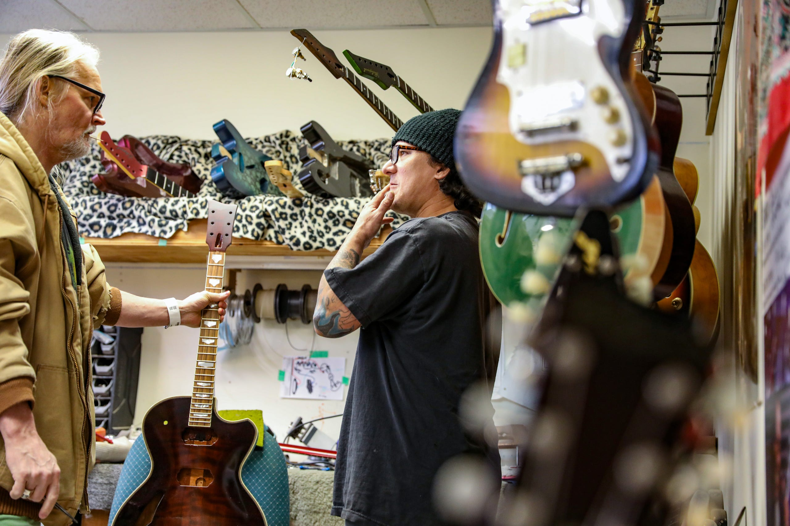 """Gabriel Currie, 52, of Detroit grew up in Los Angeles but moved to Detroit in 2017 with his family to continue making hand-crafted guitars with his company that he founded Echopark Guitars and works in his studio in the Old Redford neighborhood of Detroit on Nov. 12, 2020. Currie recently donated """"The Salt of Detroit"""" guitar that he made from 100-year-old trees submerged in Lake Michigan to Ann Delisi of WDET radio. The electric guitar will be raffled off and features drawings of famous guitarists created by Detroit artist Sabrina Nelson."""