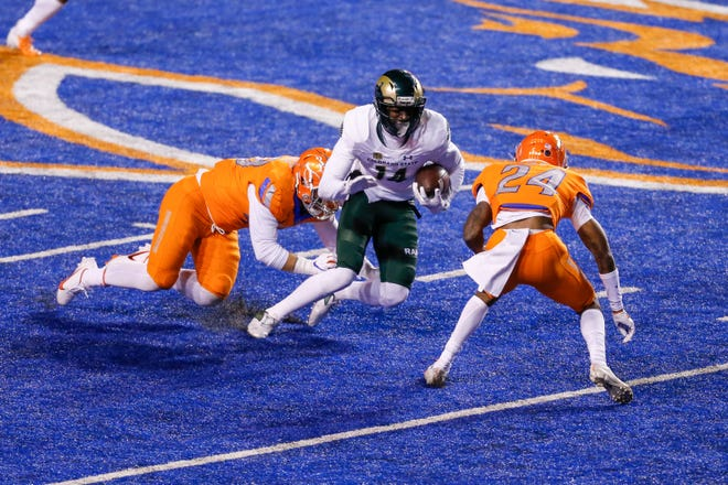 Colorado State wide receiver Nate Craig-Myers (14) turnsup field after a catch as Boise State cornerback Damon Cole (24) moves in for the tackle during the fourth quarter of an NCAA college football game Thursday, Nov. 12, 2020, in Boise, Idaho. Boise State won 52-21. (AP Photo/Steve Conner)
