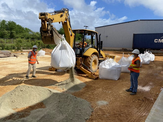 Mega United Construction workers open and spread recycled glass sand delivered to the GCA Trades Academy in Tiyan for a pilot program by the Zero Waste Guam Working Group. The glass sand partially replaces coral to construct the new parking lot.