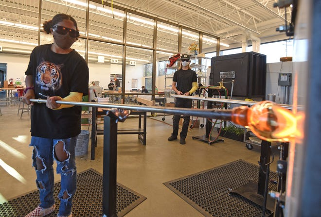 Aspen Payne heats glass in an oven Thursday before forming it in class at the Mansfield Art Center.