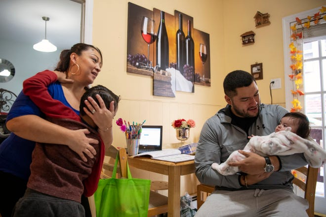 (Left) Luz Vanegas and her son Jacob Bravo, 6, look on as Eduardo Argueta holds his daughter (Vanegas' granddaughter) Emma at Vanegas' home in North Bergen on Friday, November 13, 2020. Vanegas' life turned upside down this summer when her daughter, Estefania, gave birth to her first grandchild and suffered a heart attack during delivery leaving her in a coma. Vanegas not only worried about her daughter, but also began to take care of her new granddaughter, Emma, while her father works and they figure out what happened to Estafania. Meanwhile, Vanegas is also facing deportation.