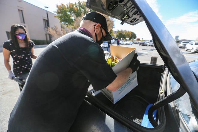 Jessie Hass fills cars with food as the Casa de Peregrinos and DACC host a drive thru food distribution at Doña Ana Community College main campus in Las Cruces on Friday, Nov. 13, 2020.