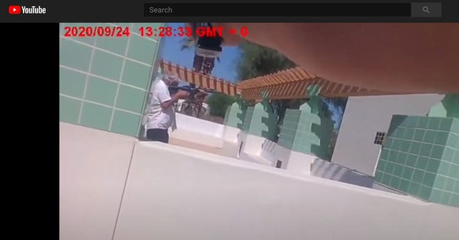 A screenshot from video taken by a Riverside County sheriff's deputy's body camera shows an armed man outside La Quinta City Hall on Sept. 24.  In this image, a deputy points his gun at the man, as the man points his rifle at another deputy, who is to the far right of the screen. The man, Randy Fedorchuk, 65, of La Quinta, was fatally shot by a deputy moments later.