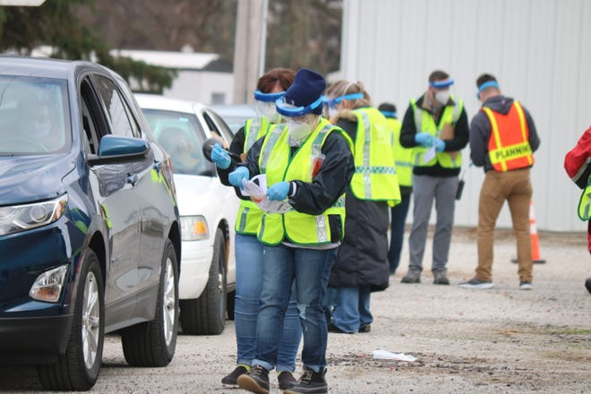 "Workers assemble testing kits for members of the public as part of the ""pop up"" testing site held at the Ottawa County Fairgrounds on Friday."