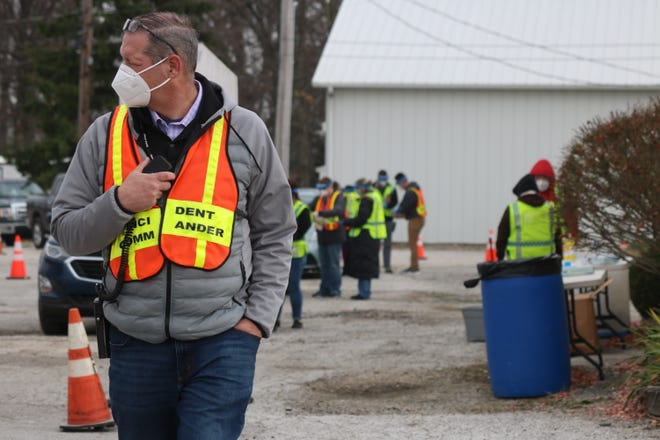 """Jerry Bingham, Ottawa County health commissioner, sends a message on the radio as he oversees """"pop up"""" testing procedures at the fairgrounds on Friday afternoon."""