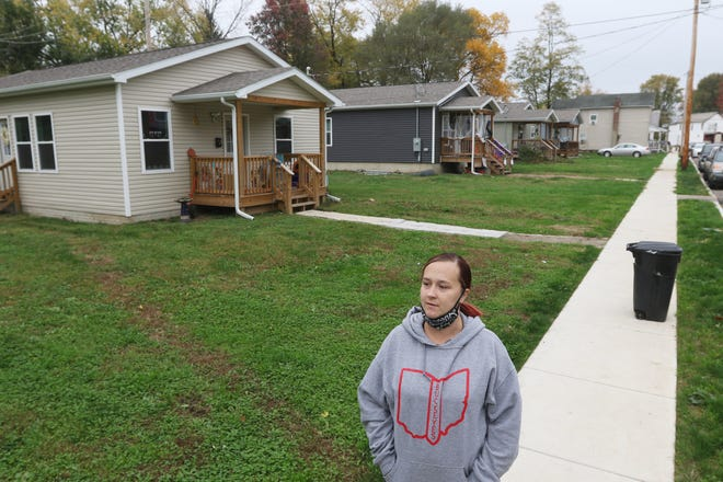 Brittany Fowler stands in front of the lot where her new home will be located on Mead Street. The house will be the fifth building by Habitat for Humanity on the street, the first four can be seen behind her.