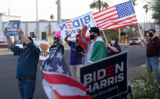 Silvana Salcido Esparza and other Biden supporters cheer while drivers honk outside Barrio Cafe in Phoenix, Arizona, Nov 7, 2020.