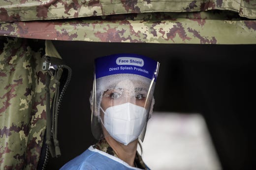 Army medical personnel, wearing a protective suit, works at a quick coronavirus testing area which was set up to ease the pressure on hospital emergency wards, following the surge of COVID-19 case numbers, in Milan, Italy, Friday, Nov. 13, 2020.