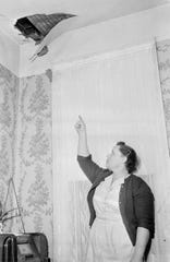 Ann Hodges points to a hole in the ceiling of her Sylacauga, Alabama, home where an approximately 8-pound meteorite crashed through her roof, hit her radio and struck her on the hip as she was napping on Nov. 30, 1954.