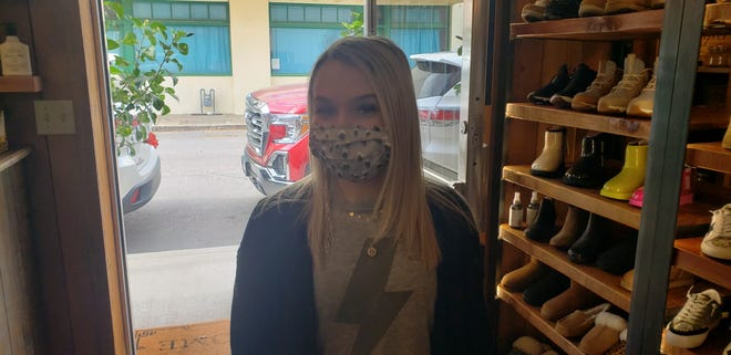 Kaitlyn England, sales associate at The Rage, wears a chain connected to her mask. The chain allows masks to hang down when they are not in use instead of being stored in a pocket or purse.