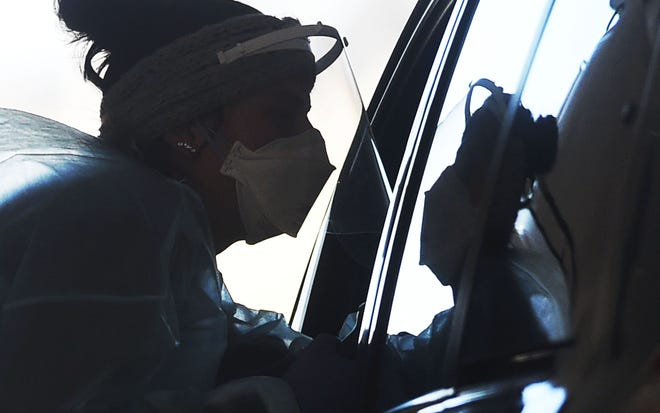 A registered nurse from Testiowa reaches into a car to take a nasopharyngeal swab from a person at a drive-through COVID-19 testing station at Iowa State University Research Park Friday, Nov. 13, 2020, in Ames, Iowa.