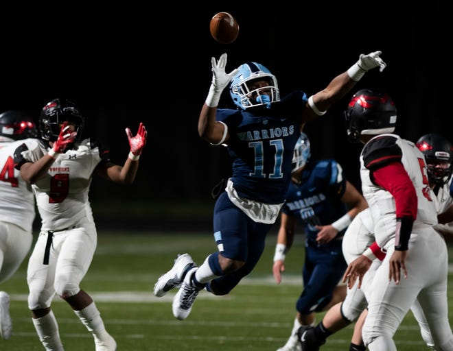 Central Valley's Amarian Saunders (11) goes up in the air to block an Elizabeth Forward pass during the WPIAL Class 3A football championship at North Allegheny High School.