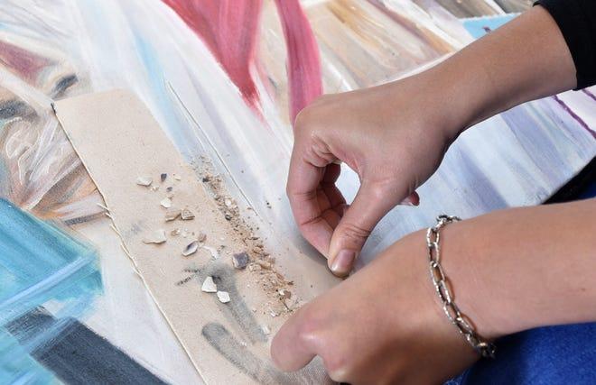 Wampanoag artist Natasha Frye glues pieces of quahog shells to her painting.