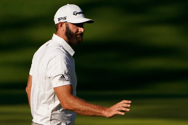 Dustin Johnson waves after putting on the 10th hole during the third round of the Masters on Saturday.