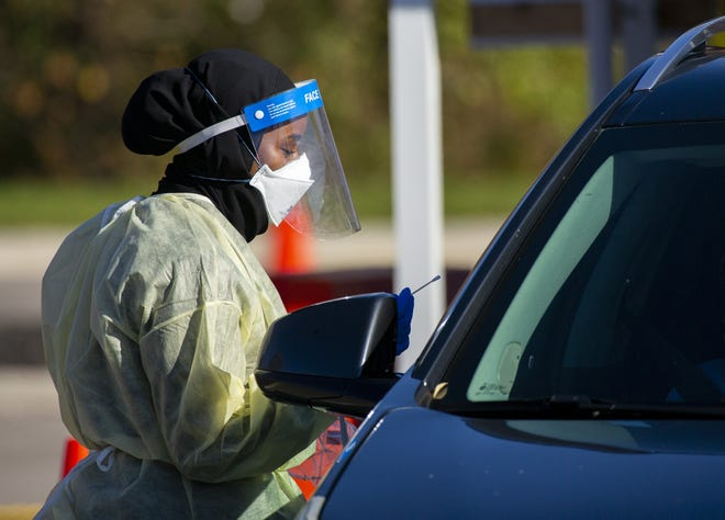 Nawal Ali, a licensed practical nurse, administers a COVID-19 test at the drive-through coronavirus testing site on the OhioHealth David P. Blom Administrative Campus in Columbus on Monday, Nov. 9, 2020.