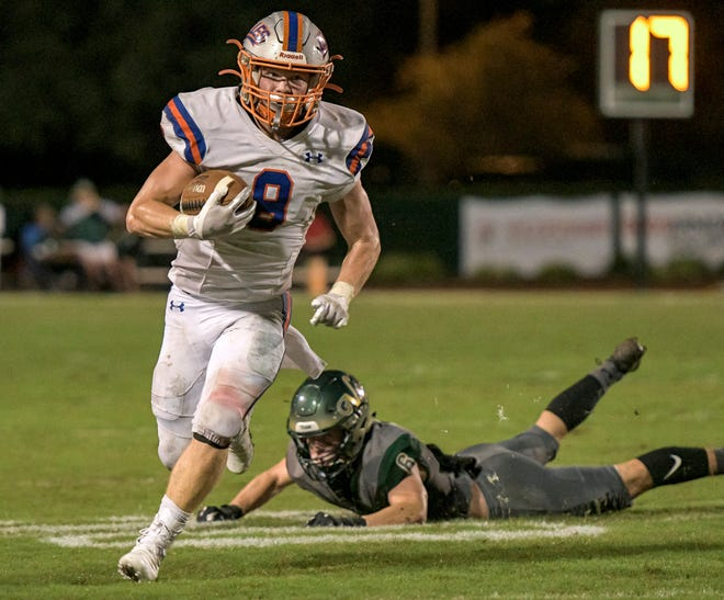 Jacksonville Bolles' Kade Frew (8) evades The Villages' Alec O'Rourke (6) on his way to a touchdown at a Class 4A-Region 2 quarterfinal against The Villages Friday at The Range. [PAUL RYAN / CORRESPONDENT]