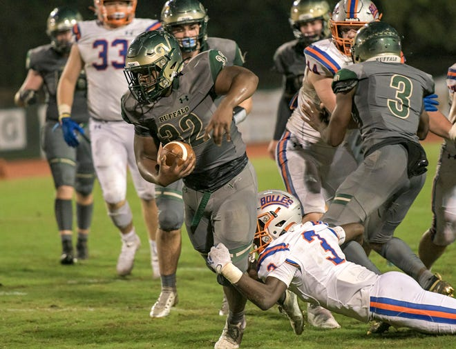 The Villages running back Ed Williams (32) powers ahead for yardage during Friday's Class 4A-Region 2 quarterfinal game against Jacksonville Bolles at The Range in The Villages. [PAUL RYAN / CORRESPONDENT]