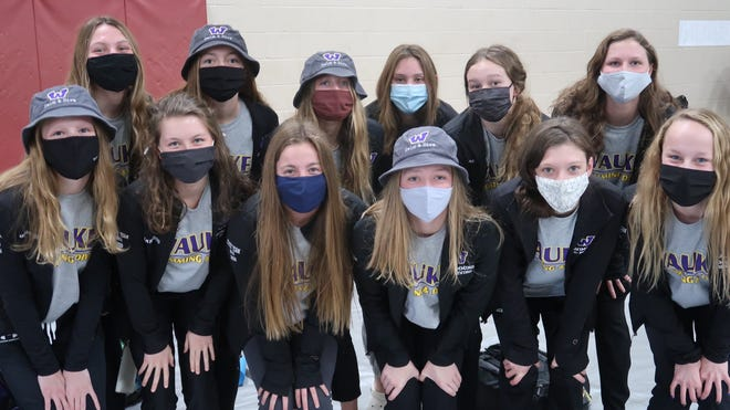 Members of the Waukee girls swim team pose for a photo before the start of the state swimming preliminaries on Friday, Nov. 13.