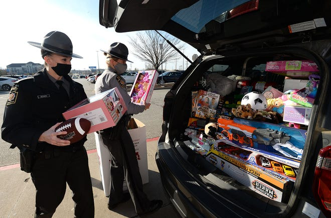 Pennsylvania State Police Troopers Cindy Schick, left, and Heather Kittle collect toys Saturday at the Walmart in Summit Township. The troopers and local U.S. Marines were collecting for the annual Toys for Tots gift giveaway.