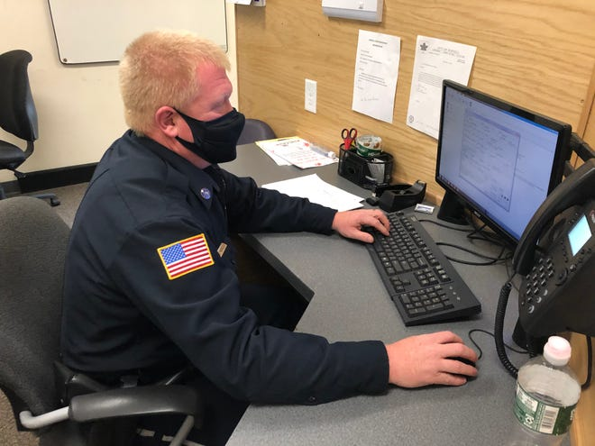 Hornell Police officer Mike Hoyt is masked up while studying a report Saturday at police headquarters.