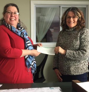 Tracy Hardekopf, executive director of the Homeless Center of Strafford County, accepts a check for $3,000 from Rochester Runners Club race director Regina Flynn following the 2018 Free Fall 5K. This year's 19th annual race will be held Thanksgiving morning with a virtual option.