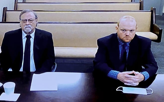 In this image made from video, from left, father and son, Gregory and Travis McMichael, accused in the shooting death of Ahmaud Arbery in Georgia on Feb. 2020, listen via closed circuit tv in the Glynn County Detention center in Brunswick, Ga., on Thursday, Nov. 12, as lawyers argue for bond to be set at the Glynn County courthouse. The McMichaels chased and fatally shot Ahmaud Arbery, a 25-year-old Black man, after they spotted him running in their neighborhood just outside the port city of Brunswick.