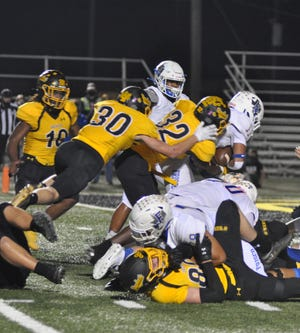 Denison's Jakalen Fields (32) and Lane Tharp go to tackle Frisco's Donta' Reece during District 7-5A (II) play at Munson Stadium.