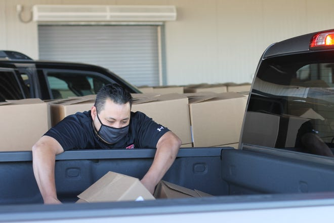 Food boxes are being loaded into a vehicle by a volunteer at the South Plains Food Bank.