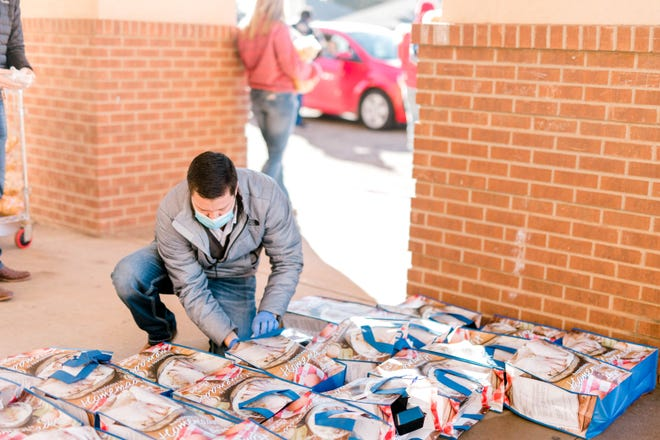 A volunteer at Lubbock Impact prepares food bags for clients. Lubbock Impact is one of several local food banks that have had resources stretched thin during the COVID-19 pandemic.