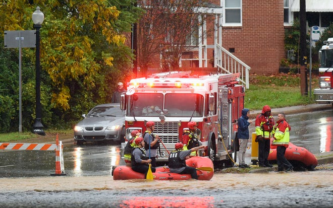 Charlotte Fire water rescue stand at the ready on West Boulevard during a heavy rain in Charlotte, N.C., on Thursday.