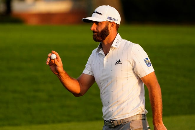 Dustin Johnson holds up his ball on the 18th green after his third round of The Masters on Saturday in Augusta, Georgia. Johnson leads by four shots heading into the final round.