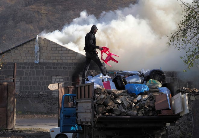 A man loads possessions on his truck after setting his home on fire, in an area once occupied by Armenian forces but is soon to be turned over to Azerbaijan, in Karvachar, the separatist region of Nagorno-Karabakh, on Friday. Under an agreement ending weeks of intense fighting over the Nagorno-Karabakh region, some Armenian-held territories adjacent to the region are passing to Azerbaijan.